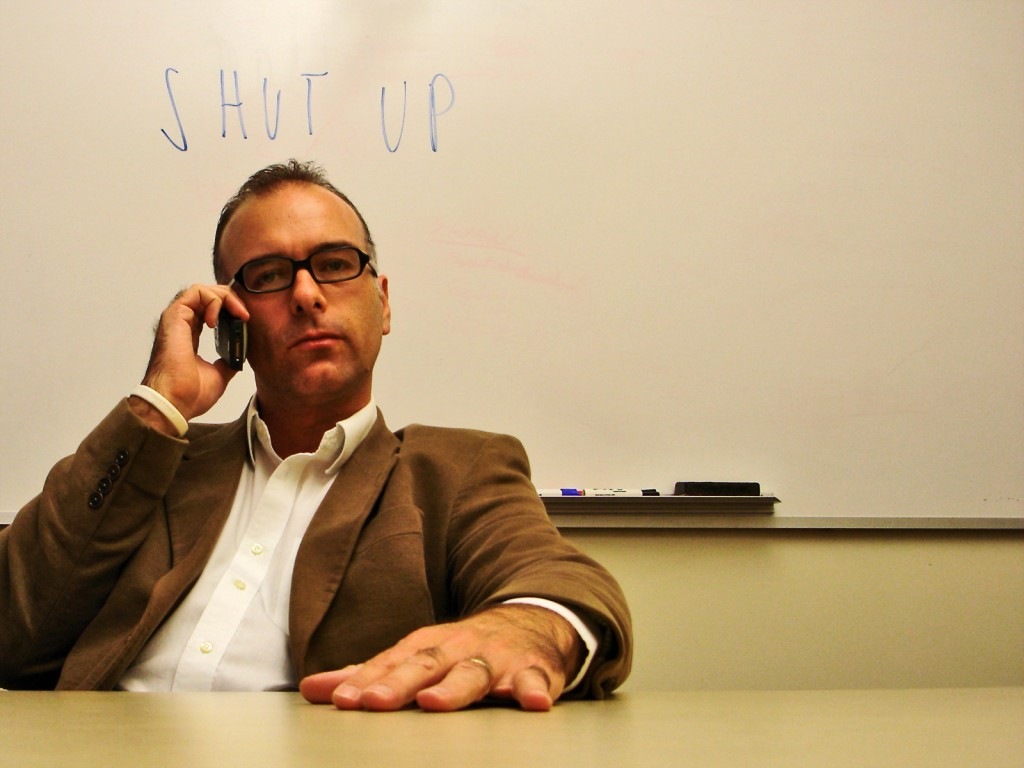 Man on phone with 'shut up' on whiteboard behind him